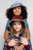 šťastný mezirasové děti v módní oblečení a klobouky objímající a při pohledu na kameru izolované na šedé