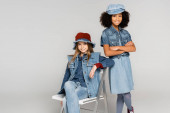 fashionable african american girl standing with crossed arms near friend sitting on chair on grey