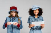 joyful interracial kids in fashionable denim clothes and hats using smartphone and digital tablet isolated on grey