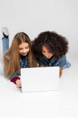 veselé mezirasové přátelé v džínové oblečení pomocí notebooku při ležení na šedé