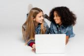 šťastný mezirasové dívky v módní džínové oblečení usmívat se na sebe při ležení na šedé poblíž notebooku