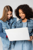 joyful interracial friends in stylish denim clothes using laptop isolated on grey