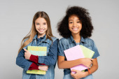 joyful, trendy interracial schoolgirls holding books and smiling at camera isolated on grey