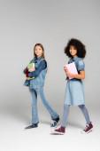 trendi fajok közötti iskolás lányok farmer ruhák és gumicipő séta tankönyvek szürke
