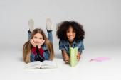 veselé školáci se usmívají na kameru, zatímco leží s učebnicemi na šedé