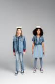teljes hosszúságú kilátás divatos fajok közötti iskolás lányok álló könyvek a fejek szürke