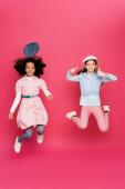 vzrušené mezirasové dívky ve stylovém jarním oblečení levitující na růžové