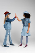 full length view of multicultural girls in denim clothes giving high five on grey