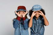 joyful multicultural friends in denim clothes and hats showing eyeglasses with hands isolated on grey
