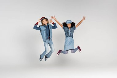 Full length view of excited multicultural girls in trendy clothes levitating on grey stock vector