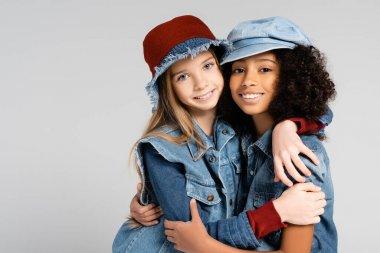 Joyful interracial girls in stylish denim clothes embracing isolated on grey stock vector