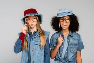 Cheerful, stylish interracial girls holding paper cut spectacles and grimacing isolated on grey stock vector