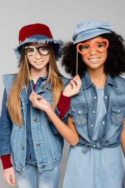 Stylish interracial girls with paper cut eyeglasses smiling at camera isolated on grey stock vector