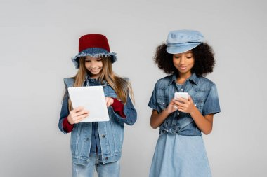 Smiling multicultural girls in denim clothes and hats using gadgets isolated on grey stock vector