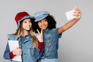 Happy african american girl taking selfie with trendy friend showing victory gesture isolated on grey stock vector