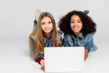 Pleased, fashionable interracial girls smiling at camera while lying near laptop on grey stock vector