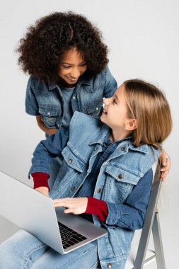 Cheerful african american girl in denim clothes near happy friend sitting on chair with laptop isolated on grey stock vector