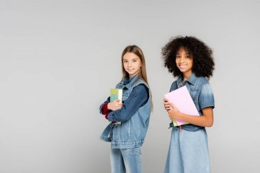 Two happy multicultural schoolkids in denim clothes standing with books isolated on grey stock vector