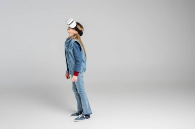 Full length view of amazed girl in stylish denim clothes and vr headset standing on grey stock vector