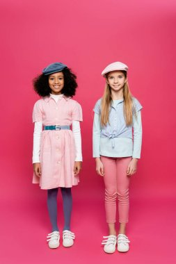 Full length view of two happy interracial girls in trendy clothes posing on pink stock vector