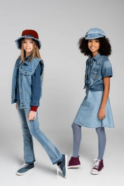Two interracial girls in fashionable denim clothes and hats posing on grey stock vector