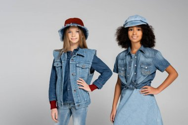 Fashionable interracial kids in denim clothes and hats posing with hands on hips on grey stock vector