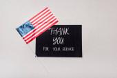 Ansicht der amerikanischen Flagge in der Nähe der Karte mit Dankeschön für Ihren Service-Schriftzug auf grauem Hintergrund