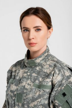 Brunette soldier looking at camera isolated on grey stock vector