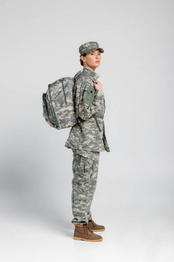 Soldier in uniform with backpack looking at camera on grey background stock vector
