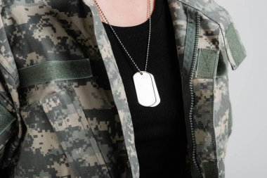 Cropped view of silver dog tags on neck of woman in military uniform isolated on grey stock vector
