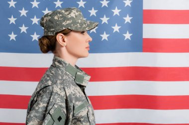 Side view of woman in camouflage uniform near american flag at background stock vector