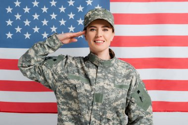Smiling soldier saluting near american flag at background stock vector