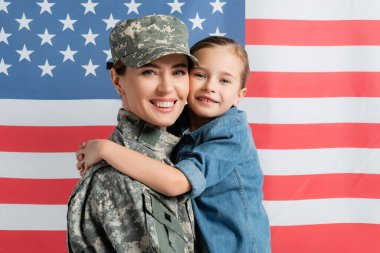 Smiling girl hugging mother in military uniform near american flag at background stock vector