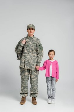 Soldier with backpack holding hand of daughter on grey background stock vector