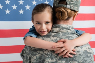 Happy kid hugging mother in camouflage near american flag at background stock vector