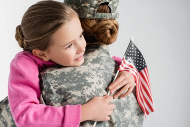 Smiling daughter holding american flag and hugging mother in military uniform isolated on grey stock vector