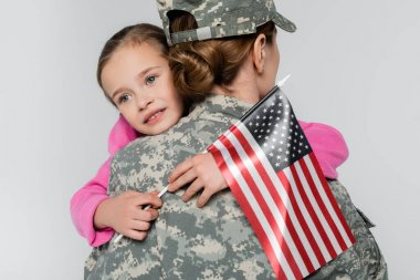 Smiling girl hugging mother in camouflage and holding american flag isolated on grey stock vector
