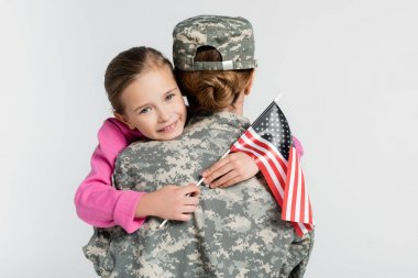 Cheerful kid with american flag embracing mother in military uniform isolated on grey stock vector