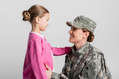 Smiling mother in military clothes hugging daughter isolated on grey stock vector