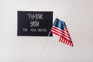 Top view of card with thank you for your service lettering and american flag on grey background stock vector