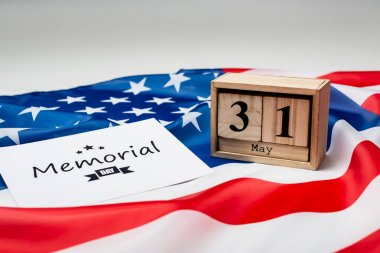 Card with memorial day lettering, wooden calendar and american flag on grey background stock vector