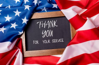 Top view of thank you for your service lettering on chalkboard on american flag stock vector