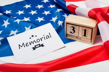 Wooden calendar and card with memorial day lettering on american flag on grey background stock vector