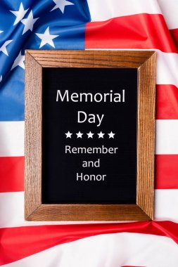 Top view of memorial day remember and honor lettering on chalkboard on american flag stock vector