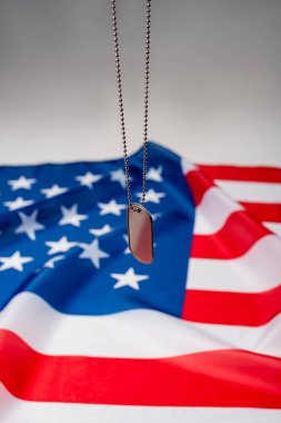 Close up view of dog tag near american flag blurred on grey background stock vector