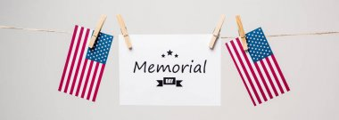 Memorial day lettering on card near american flags on rope isolated on grey, banner stock vector