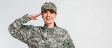 Cheerful soldier saluting and looking at camera isolated on grey, banner stock vector