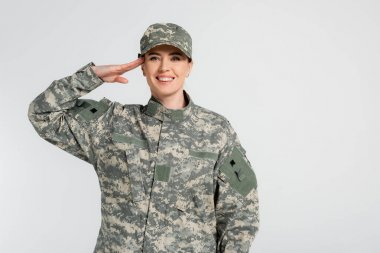 Woman in camouflage clothes saluting isolated on grey stock vector