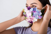 young woman wearing medical mask with blooming flowers isolated on white
