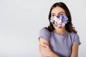 mladá žena v lékařské masce s květy izolované na bílém